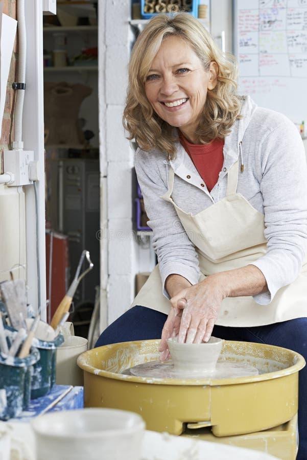 O retrato da mulher madura que trabalha em oleiro roda dentro o estúdio imagens de stock royalty free