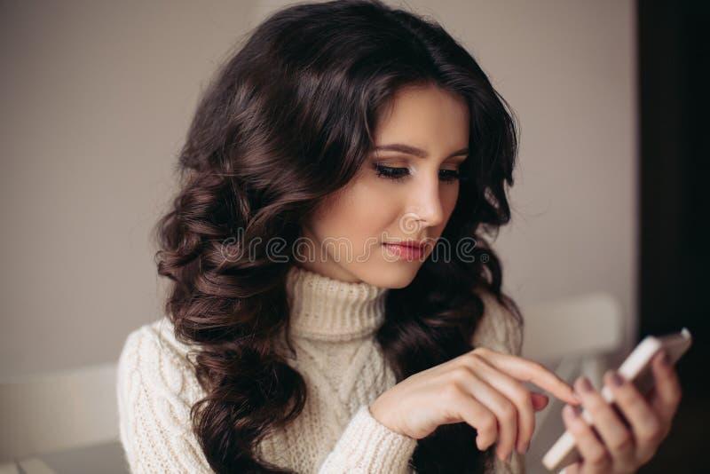 O retrato da mulher moreno bonita nova que fala no telefone, escreve SMS Estudante triste com o telefone à disposição fotografia de stock royalty free