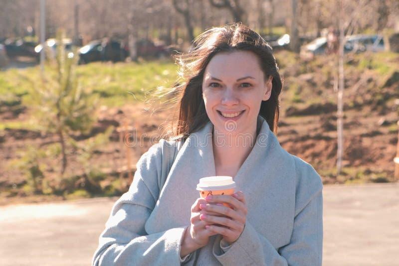 O retrato da mulher moreno nova no revestimento anda no parque da cidade e bebe o café primavera fotografia de stock royalty free