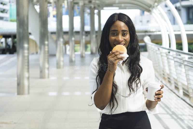 O retrato da mulher negra feliz do negócio come no fast food da posse foto de stock royalty free