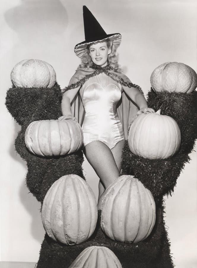 O retrato da mulher no traje 'sexy' da bruxa cercado por abóboras na grama arquiva imagens de stock