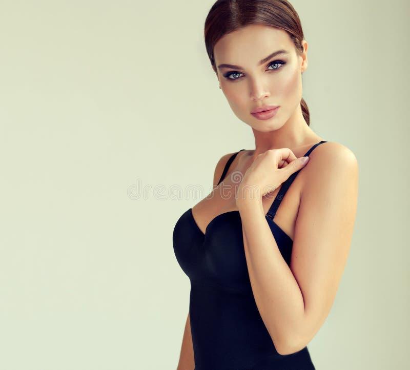 O retrato da mulher nova, sexual vestiu-se no corpo preto sedutor Composição e cosmetologia imagens de stock royalty free