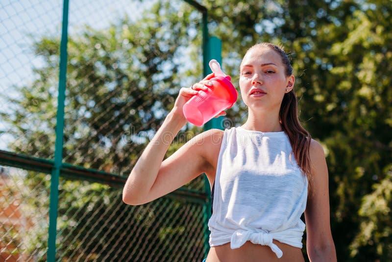 O retrato da mulher 'sexy' nova desportiva que bebe a água fresca da garrafa em esportes de um verão coloca fora foto de stock royalty free