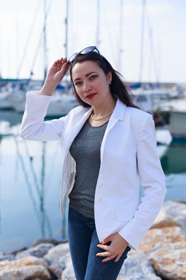 O retrato da mulher vestiu-se no estilo náutico no porto do iate foto de stock