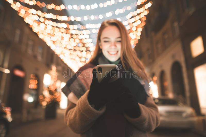 O retrato da noite de uma menina bonito guarda um smartphone em seus mãos e olhares na tela foto de stock