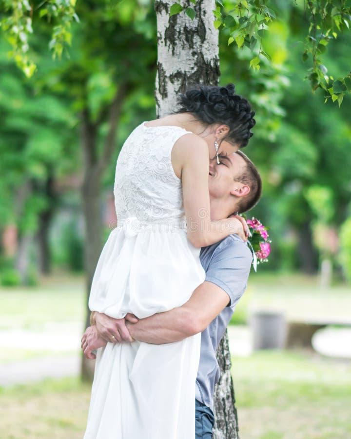 O retrato da noiva fêmea dos pares novos bonitos e o noivo do homem que beija no verão estacionam Marido do homem que guarda a es foto de stock royalty free