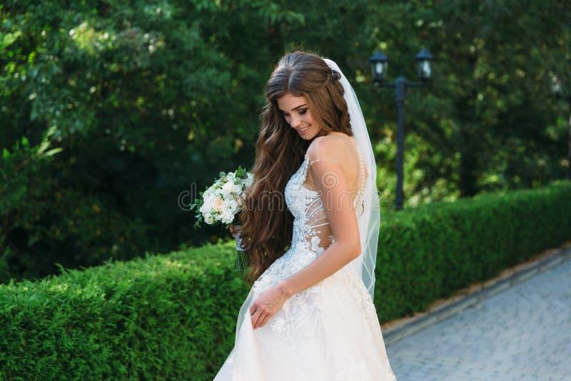 O retrato da noiva nova bonita com o smite bonito no ramalhete branco da posse do vestido de casamento das flores em suas mãos es imagem de stock royalty free