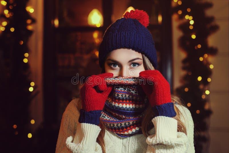O retrato da rua da noite da mulher bonita nova no inverno morno à moda clássico fez malha a roupa com o lenço que cobre a imagem de stock royalty free