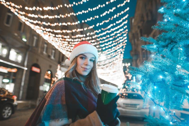 O retrato da rua de uma mulher que veste um chapéu do Natal está na rua perto do foto de stock royalty free