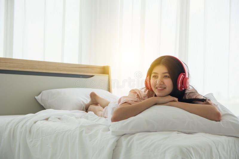O retrato da senhora de sorriso no pijama cor-de-rosa acorda a escuta a música com luz o da manhã da boa vinda do fones de ouvido foto de stock royalty free