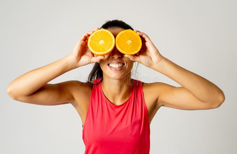 O retrato da terra arrendada engraçada e atrativa alegre da mulher cortou a laranja sobre seus olhos foto de stock royalty free