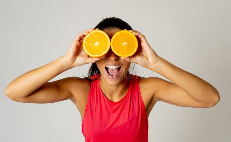 O retrato da terra arrendada engraçada e atrativa alegre da mulher cortou a laranja sobre seus olhos imagem de stock