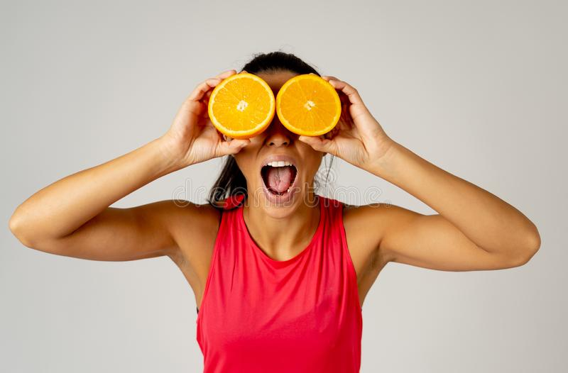 O retrato da terra arrendada engraçada e atrativa alegre da mulher cortou a laranja sobre seus olhos imagens de stock