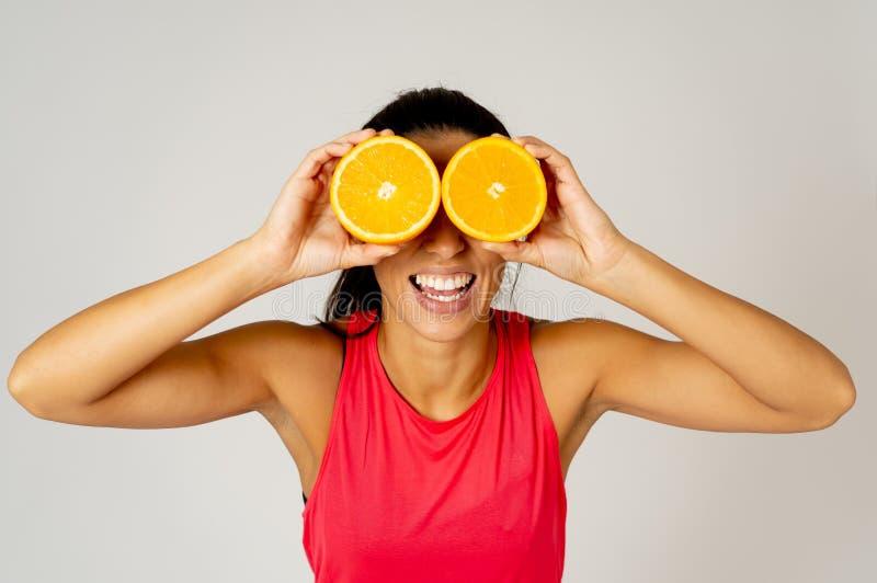 O retrato da terra arrendada engraçada e atrativa alegre da mulher cortou a laranja sobre seus olhos fotografia de stock
