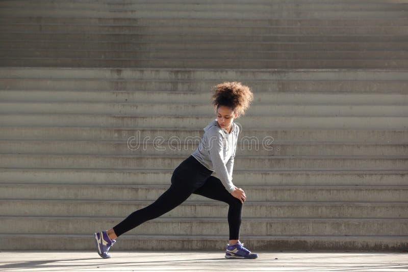 O retrato da vista lateral de uma jovem mulher que estica o pé muscles foto de stock