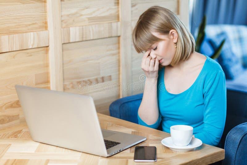 O retrato da vista lateral do freelancer triste da moça com cabelo louro do corte de cabelo do prumo no t-shirt azul está sentand imagem de stock