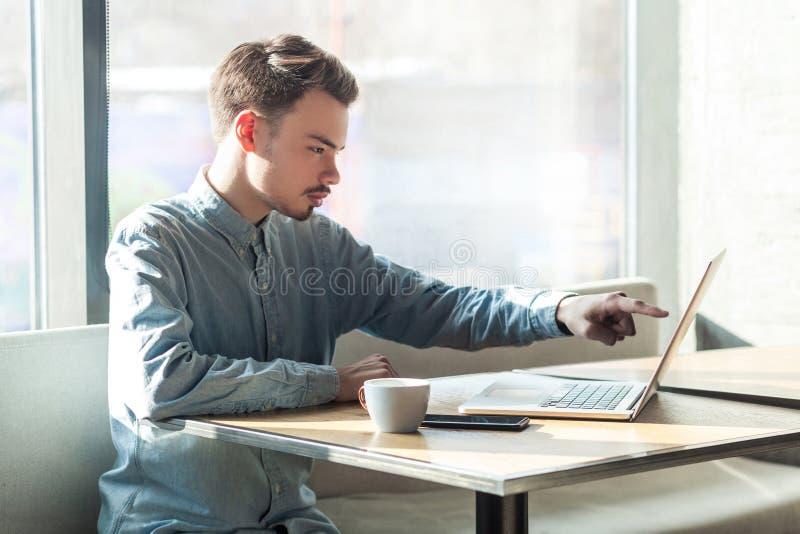 O retrato da vista lateral do homem de negócios novo sério na camisa azul é de assento e apontando no alvo no portátil dislpay co fotografia de stock