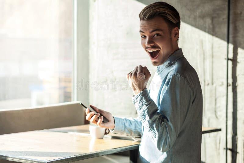 O retrato da vista lateral do sucesso feliz surpreendeu o homem novo farpado no telefone azul da terra arrendada da posição da ca imagem de stock