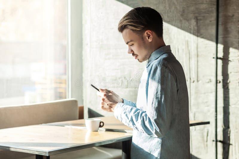 O retrato da vista lateral do sucesso sério surpreendeu o homem novo farpado na posição azul da camisa da sarja de Nimes no café, fotos de stock royalty free