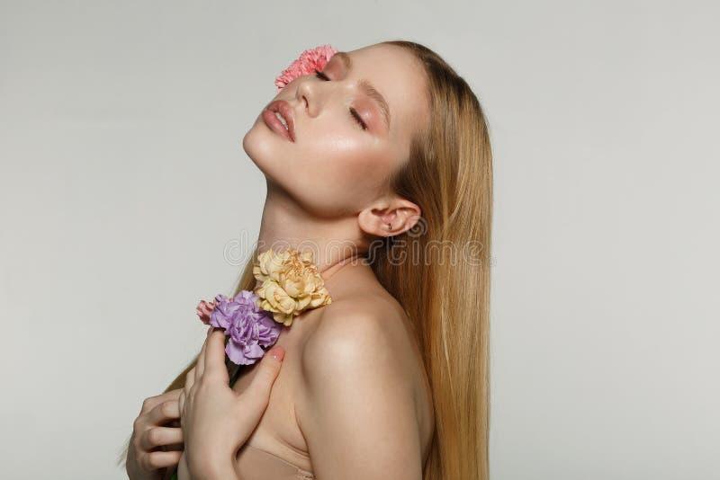 O retrato da vista lateral da menina loura nova encantador com composição perfeita e os olhos fechados, pressionou flores a seu c fotografia de stock