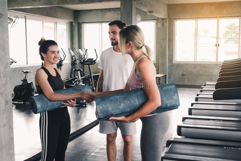 O retrato de adolescentes desportivos no Sportswear está cumprimentando o aperto de mão antes de praticar a ioga, grupo de pessoa imagem de stock royalty free