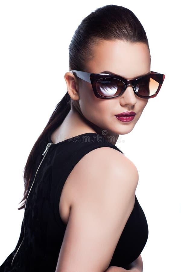 O retrato de bonito e forma a menina nos óculos de sol, sho do estúdio imagem de stock
