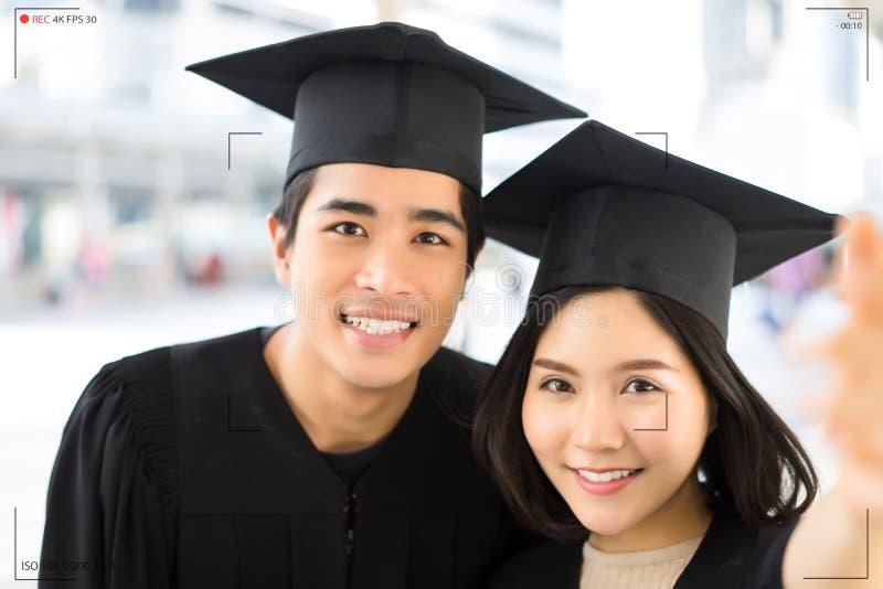 O retrato de dois estudantes de graduação felizes faz a gravação do selfie foto de stock royalty free