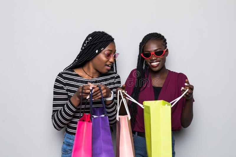 O retrato de dois excitou jovens mulheres africanas na roupa do verão que olha dentro dos sacos de compras isolados sobre o fundo fotos de stock