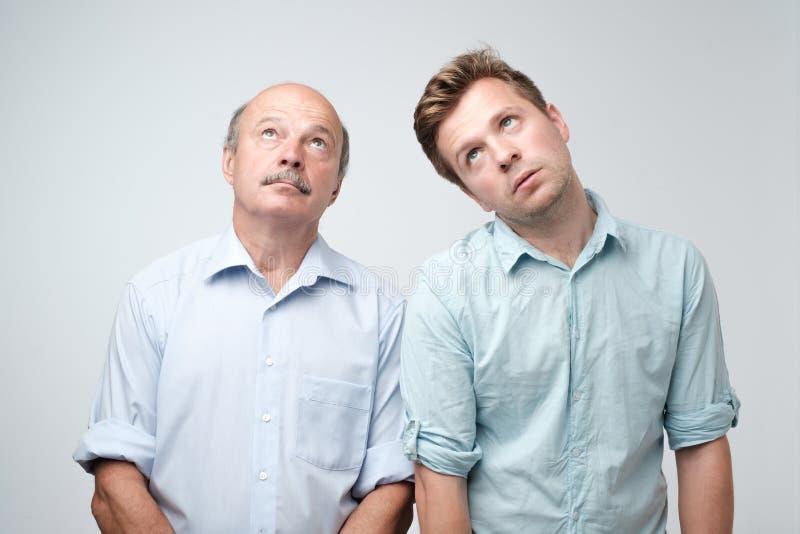 O retrato de dois homens maduros com expressão acima alimentada furada, olhares desagrada O pai e o filho são cansados e furados imagens de stock