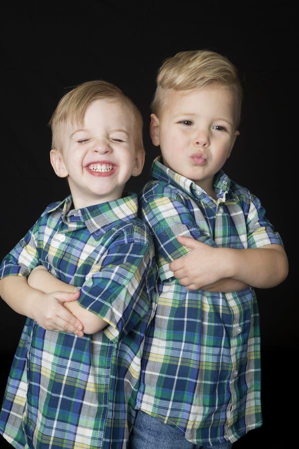 O retrato de dois meninos bonitos que estão os braços dobrou expressões engraçadas fotografia de stock