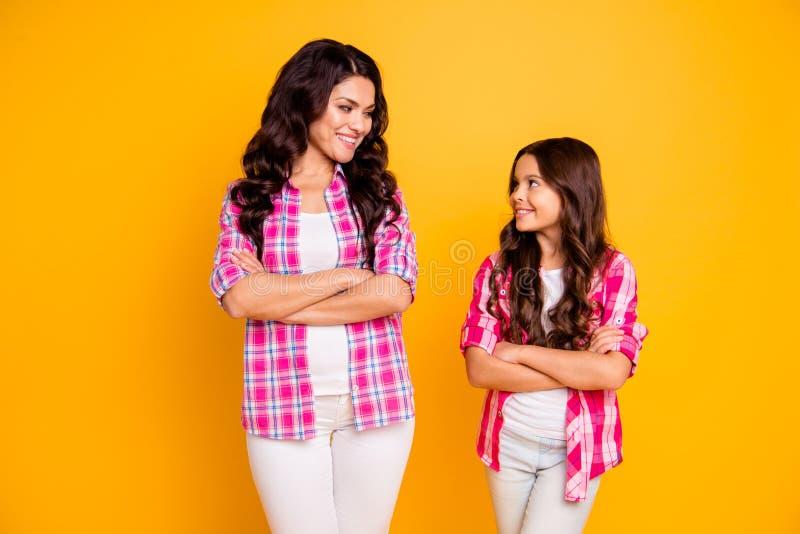 O retrato de duas meninas ondulado-de cabelo alegres bonitas atrativas devista que vestem a camisa verificada dobrou os braços qu foto de stock royalty free