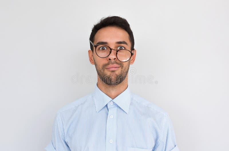 O retrato de homem confundido frustrante com restolho, olhares severos enfrenta, vestindo os espetáculos redondos que levantam so fotos de stock