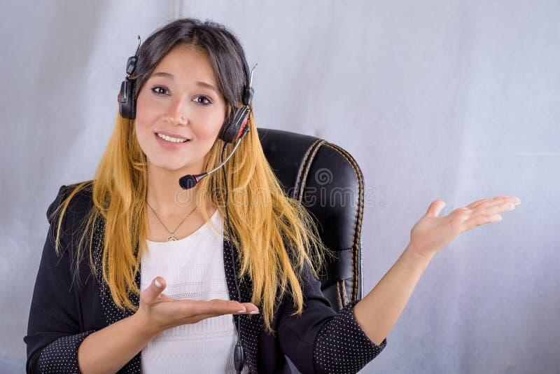 O retrato de jovens alegres de sorriso felizes apoia o operador do telefone nos auriculares que mostram a área ou a algo de espaç fotografia de stock royalty free