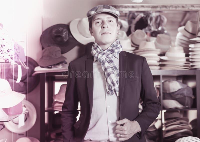 O retrato de masculino novo tenta sobre o tampão newboy no shopping fotos de stock