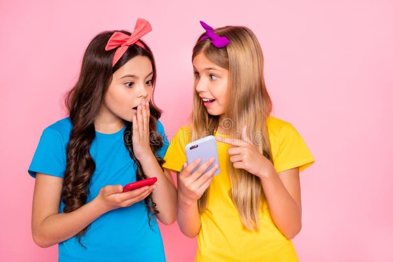 O retrato de meninas impressas veste o dispositivo à moda na moda da mão da posse do t-shirt do penteado do penteado longo das fa imagens de stock