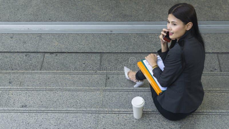 O retrato de mulheres asiáticas do negócio usa o smartphoone em exterior imagem de stock