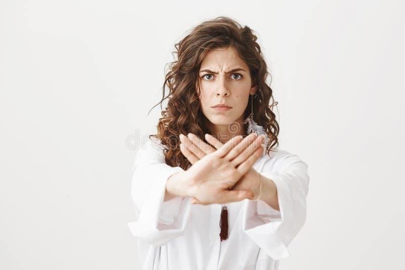 O retrato de olhar de sobrancelhas franzidas fêmea caucasiano preocupado sério ao esticar as mãos para a câmera com parada gestic imagem de stock