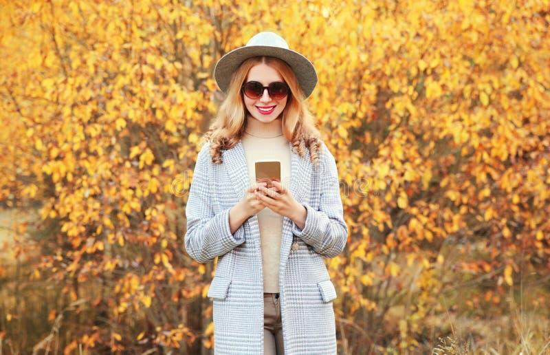 O retrato de outono é uma mulher sorridente e elegante segurando um telefone de casaco cinza, chapéu redondo em folhas amarelas imagens de stock