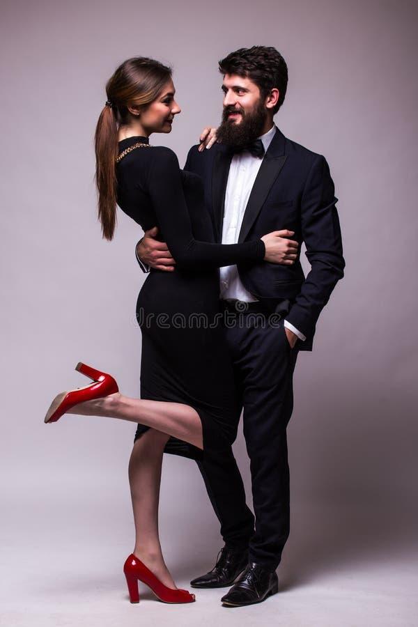 O retrato de pares novos no levantamento do amor vestiu-se na roupa clássica no backround cinzento Homem com a barba no terno, mu fotos de stock