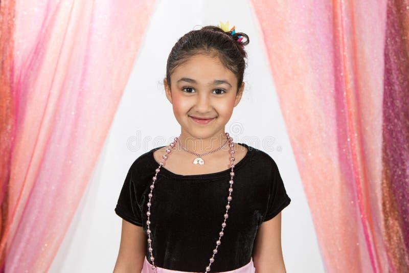O retrato de sorriso de um jogo da menina veste-se acima imagem de stock royalty free