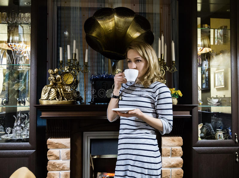 O retrato de stends de uma jovem mulher perto da chaminé, menina de sorriso feliz bebe o chá fotografia de stock