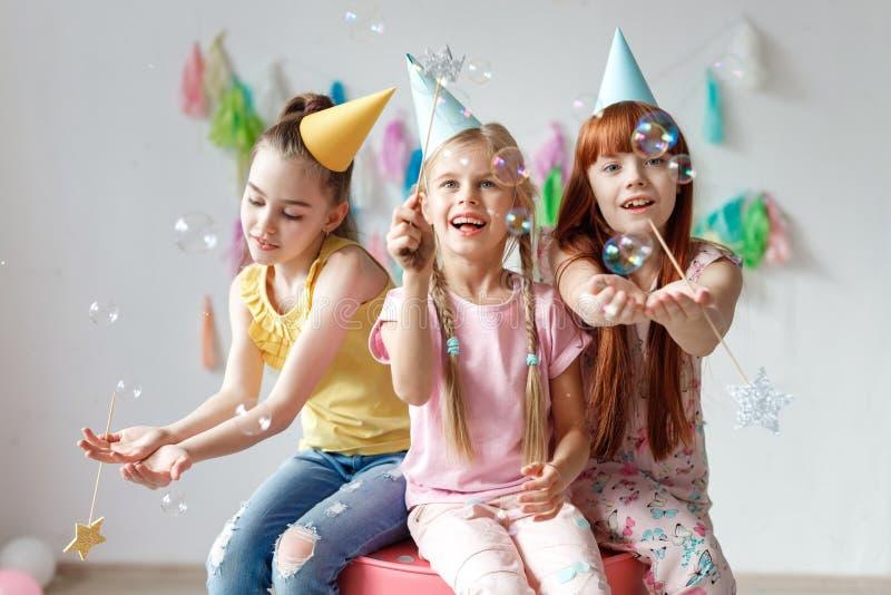 O retrato de três meninas bonitas veste tampões festivos, joga com bolhas, senta-se junto na cadeira, comemora o aniversário, sen foto de stock