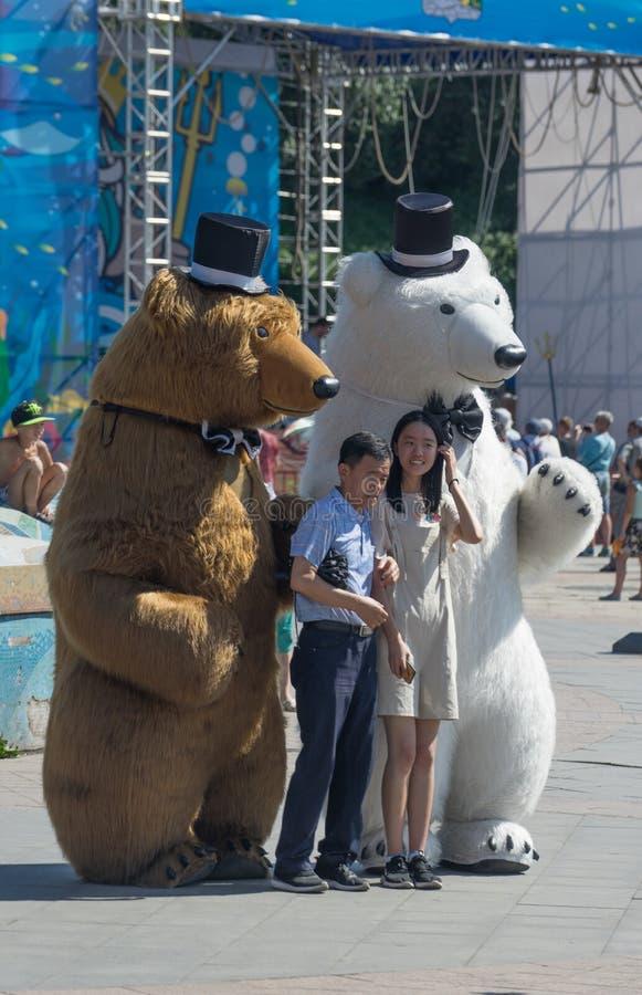 O retrato de turistas asiáticos no fundo dos povos vestiu-se nos trajes de ursos altos fotografia de stock