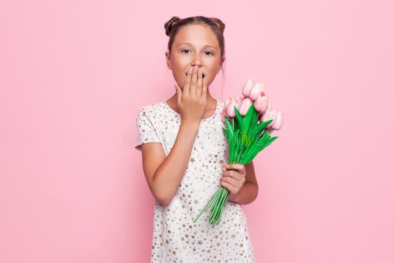 O retrato de um adolescente bonito, menina chocada cobre sua boca com sua mão, em um vestido à moda com um ramalhete das flores fotografia de stock