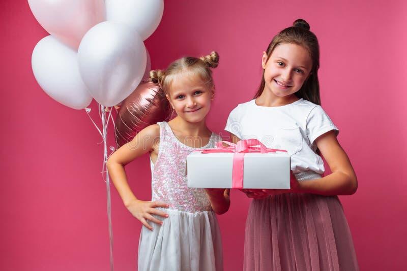 O retrato de um adolescente em um fundo cor-de-rosa, com presentes, o conceito do aniversário, um dá a uma outra menina um presen fotografia de stock