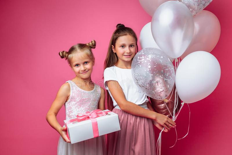 O retrato de um adolescente em um fundo cor-de-rosa, com presentes, o conceito do aniversário, um dá a uma outra menina um presen fotografia de stock royalty free