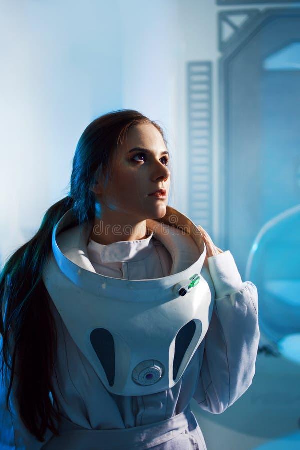 O retrato de um astronauta da mulher em um terno de espaço, sonhador olha acima Astronauta futurista a bordo a nave espacial fotos de stock