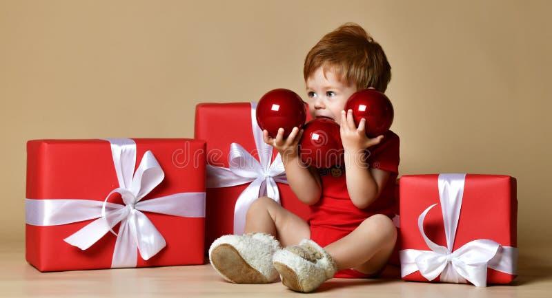 O retrato de um bebê vestiu um bodysuit vermelho com as decorações vermelhas das bolas nos presentes atuais do xmas sobre o fundo foto de stock