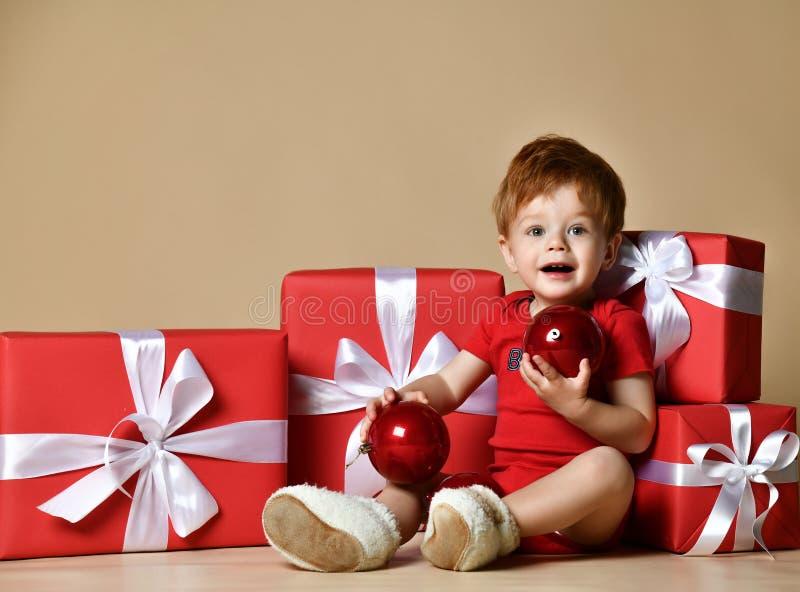 O retrato de um bebê vestiu um bodysuit vermelho com as decorações vermelhas das bolas nos presentes atuais do xmas sobre o fundo fotografia de stock