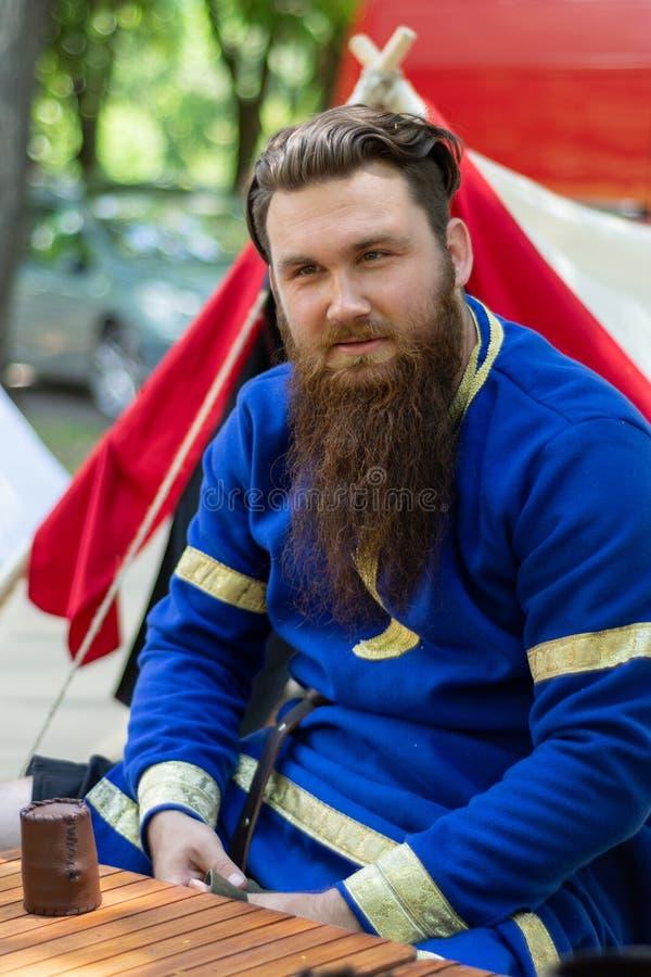 O retrato de um cavaleiro com uma barba em um terno tradicional azul senta-se foto de stock royalty free